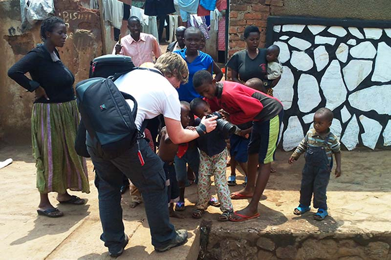 Bunki zeigt Kindern einige Fotos, Kigali, Ruanda