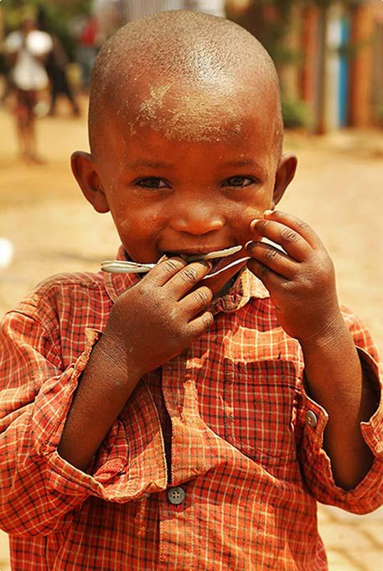 Junge kaut auf einem Plastelöffel, Kigali, Ruanda